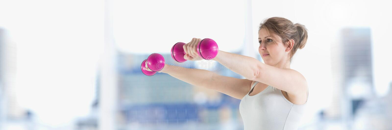 Slim healthy woman lifting weights stock photos