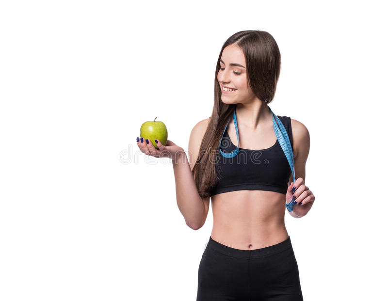 Slim and healthy young woman holding measure tape and apple isolated on white background. Weight loss and diet concept. stock image