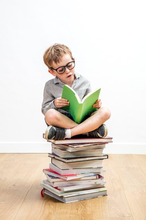 Slim jong kind die een boek op stapel van wijsheid lezen royalty-vrije stock afbeeldingen
