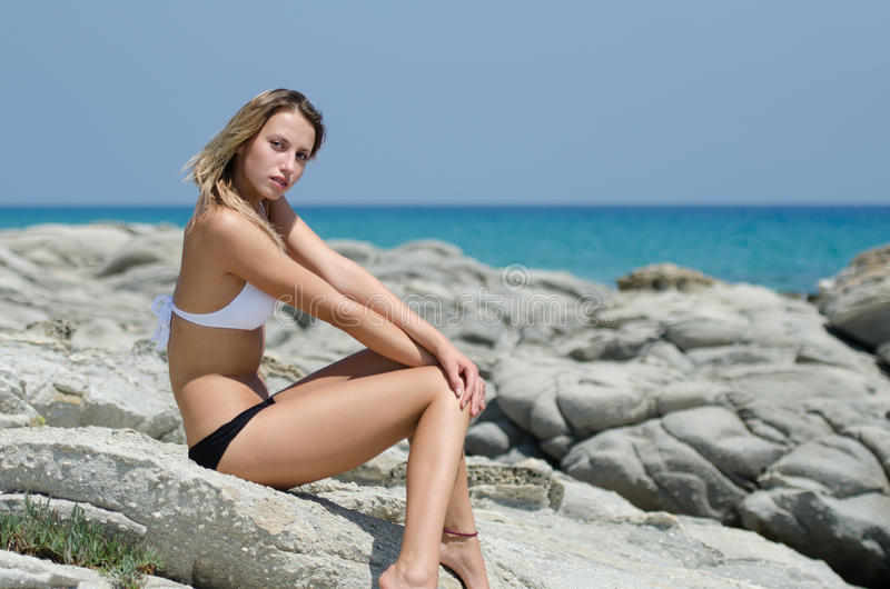 Slim lady with outstanding body sitting on rocks and displays the body with admiration. Whilst wearing a black white bikini. Sea horizon at the background royalty free stock image