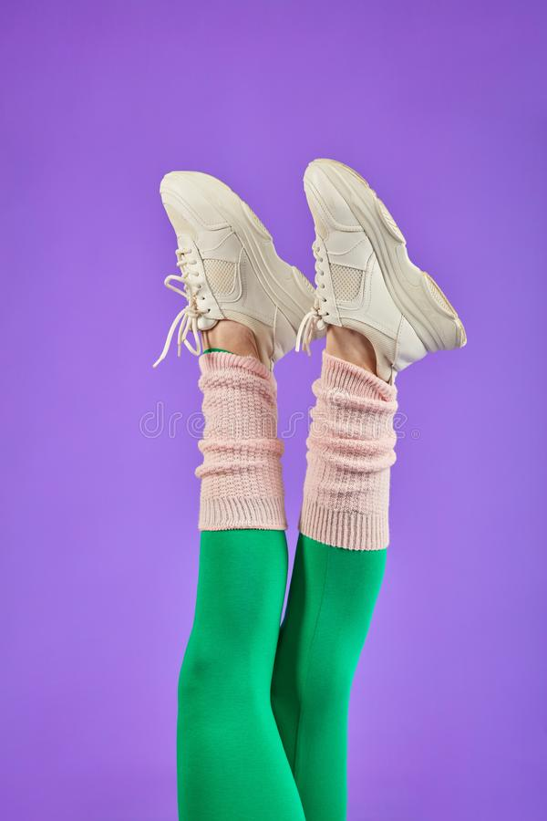 Slim legs in green leggins close up view. Close up on slim sporty legs raised up in green leggins and white sport shoes, making cross moves in air. Studio shot stock image