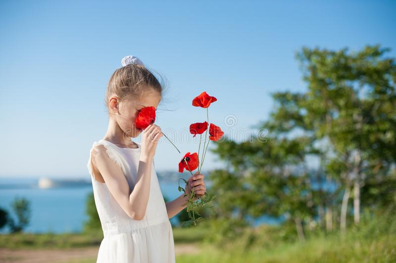 Slim little girl sniffing red flowers outdoors near sea in spring stock photography