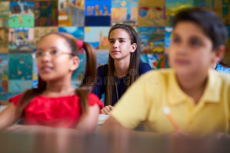 Slim Meisje die aan Leraar At School luisteren royalty-vrije stock afbeeldingen