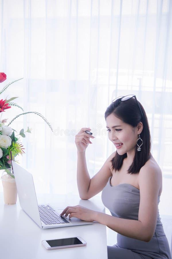 Slim meisje ` die s aan notitieboekje, Arbeidster werken die laptop in de ruimte met behulp van stock foto's