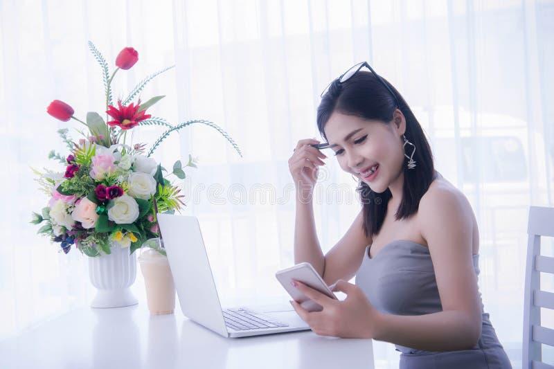 Slim meisje ` s gebruikend slimme telefoon en werkend aan laptop, gelukkige tijd stock afbeelding