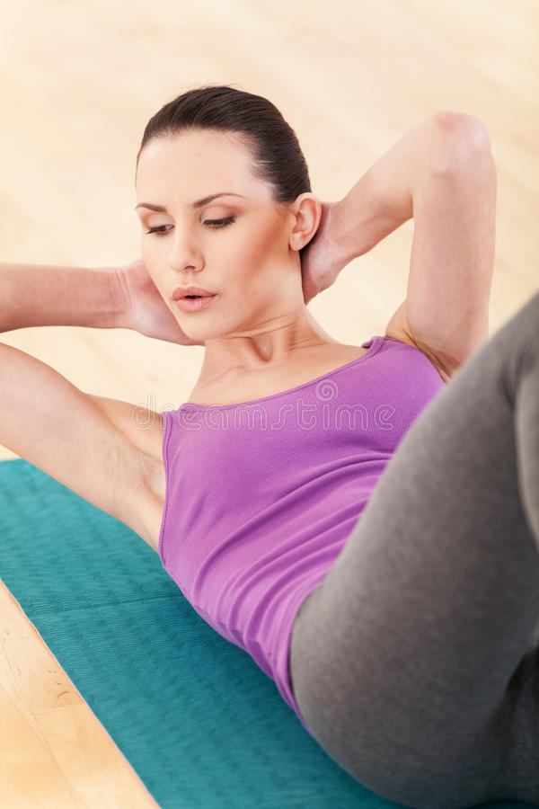Slim mid aged woman do her fitness exercises. stock photography