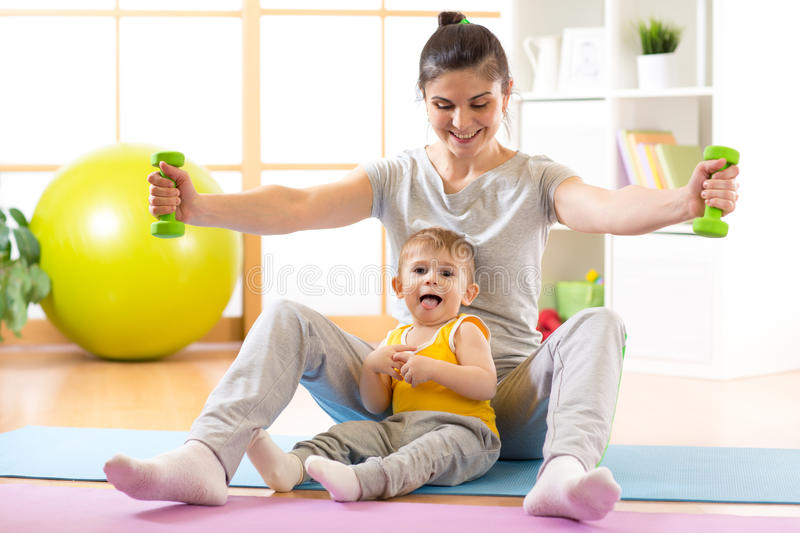 Slim mother with little kid doing gymnastics and fitness exercises. Sportive mother with little kid boy doing gymnastics and fitness exercises stock image
