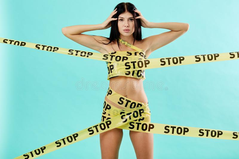 Slim naked dark-haired girl wrapped in yellow scotch tapes with inscriptions of word `stop` stands on the blue royalty free stock images