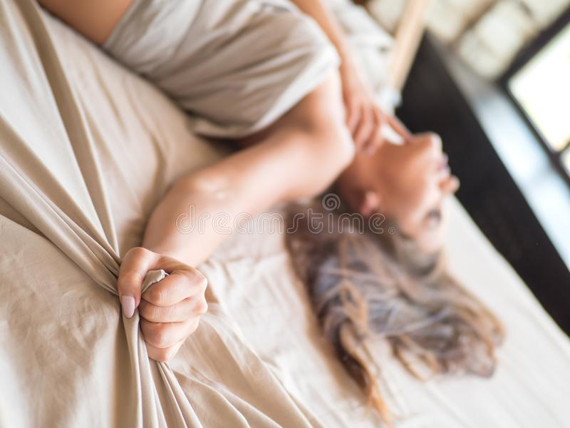 Slim, perfect and beautiful woamn on bed. Cropped image of erotically lying on bed beautiful woman in bedroom. Crumpled stock photo