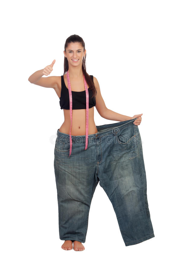 Slim pretty girl with a big trousers saying Ok royalty free stock photography