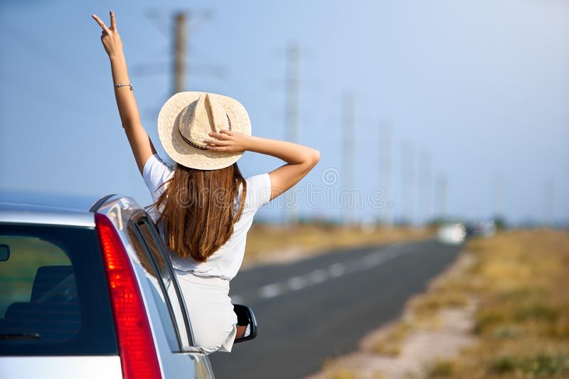 Slim pretty woman in straw hat enjoying road trip on a summer day. Excited young female raising her hand with victory stock images