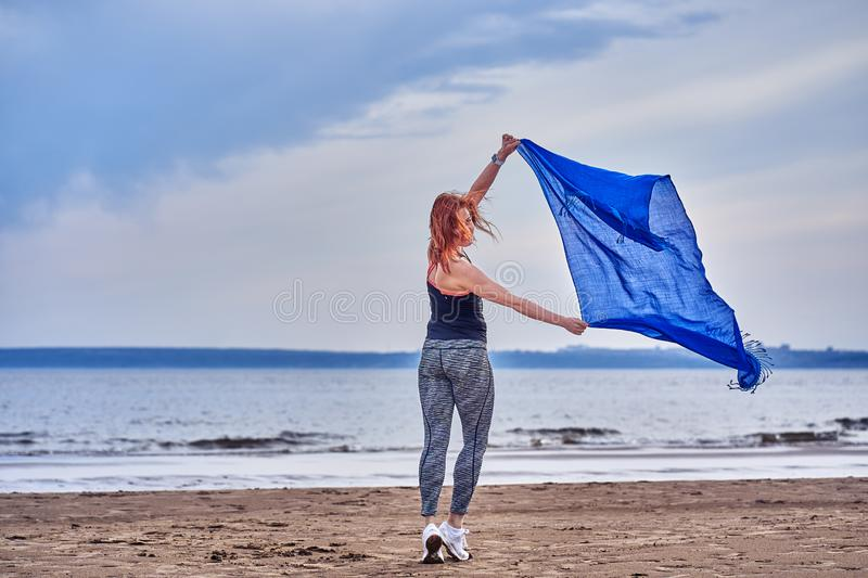 Slim red-haired middle-aged woman in sports form is engaged in dancing with a blue scarf. A woman is engaged on the sandy shore of. A large river. Cloudy summer stock photo