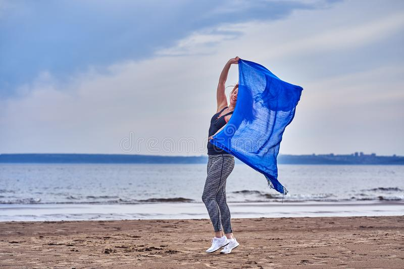 Slim red-haired middle-aged woman in sports form is engaged in dancing with a blue scarf. A woman is engaged on the sandy shore of. A large river. Cloudy summer royalty free stock photography