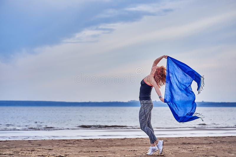 Slim red-haired middle-aged woman in sports form is engaged in dancing with a blue scarf. A woman is engaged on the sandy shore of. A large river. Cloudy summer royalty free stock photo