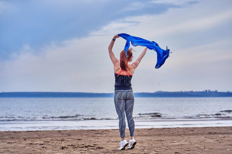 Slim red-haired middle-aged woman in sports form is engaged in dancing with a blue scarf. A woman is engaged on the sandy shore of. A large river. Cloudy summer stock photos