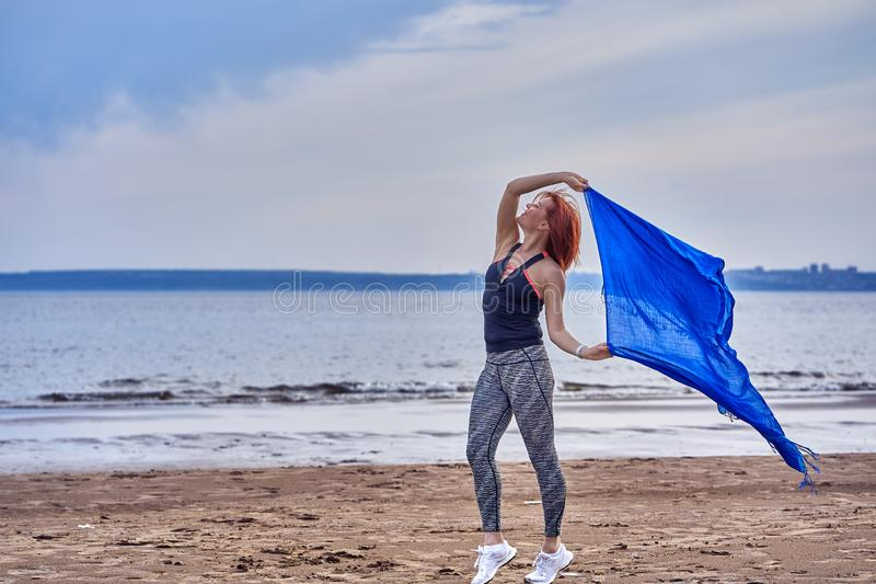 Slim red-haired middle-aged woman in sports form is engaged in dancing with a blue scarf. A woman is engaged on the sandy shore of. A large river. Cloudy summer stock images