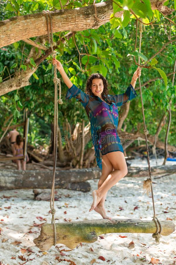 Slim sexy girl model in a swimsuit posing on a wooden swing tied to a tree. On the background of the beach of a tropical island stock photos