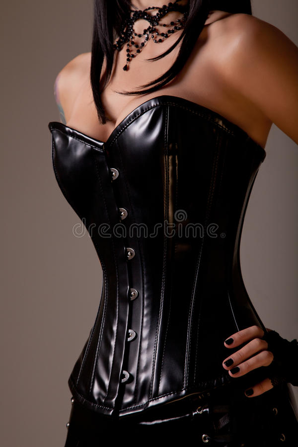 Slim woman with hourglass figure. In black leather corset, studio shot stock photos