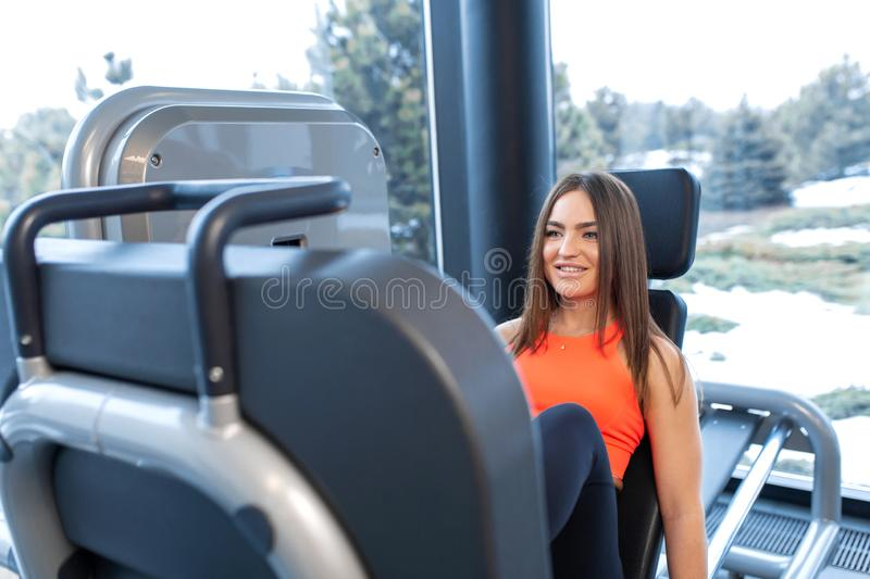 Slim smiling woman using a leg press machine and placing her legs on the platform royalty free stock image