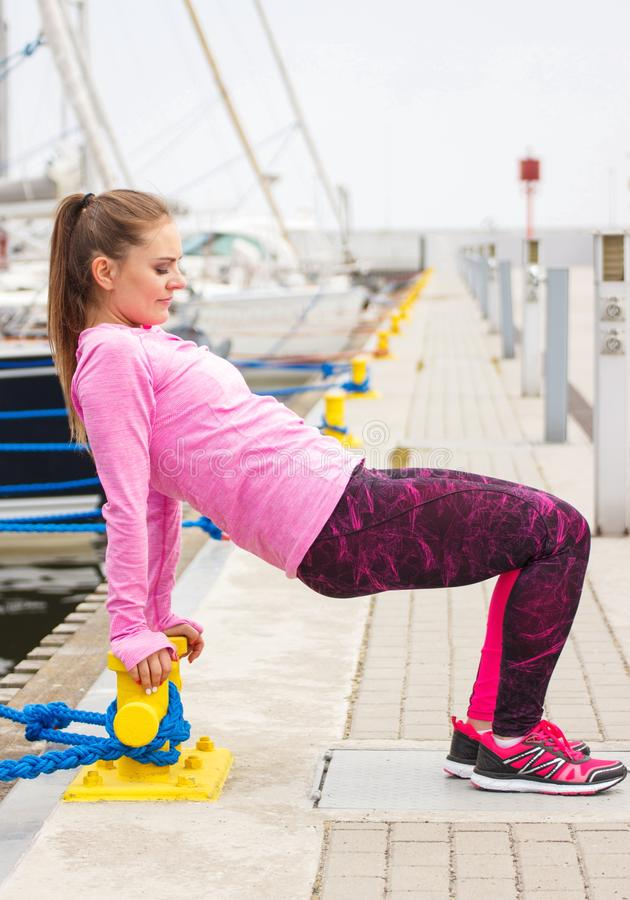 Slim girl in sports wear exercising in seaport, healthy active lifestyle on fresh air stock images