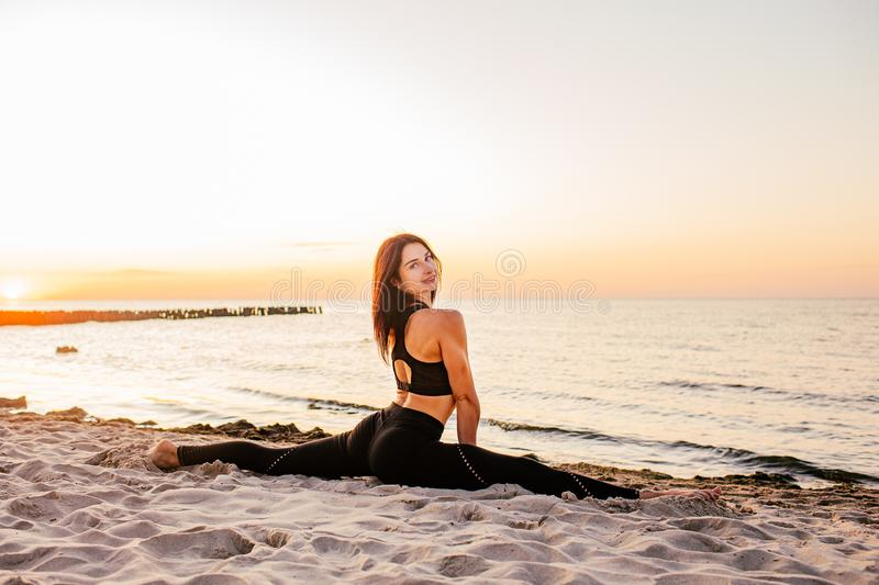 Slim strong young woman in black practicing yoga doing the splits on sand beach close-up with copy space. Sunset, summer. Healhy royalty free stock photo