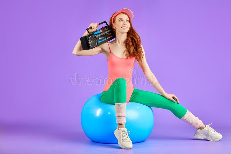 Slim student girl sits on fit ball with portable cassette player waiting to start the retro 80s dance party royalty free stock photography