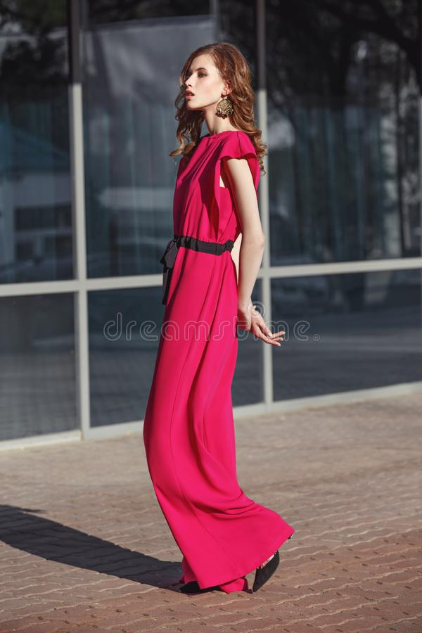 Slim stylish brunette girl dressed in fuchsia color overalls is walking in the city street on a sunny day royalty free stock photo