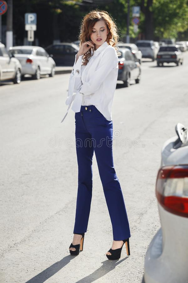 Slim stylish brunette girl dressed in white shirt and blue trousers is standing in the street on a summer day royalty free stock photos