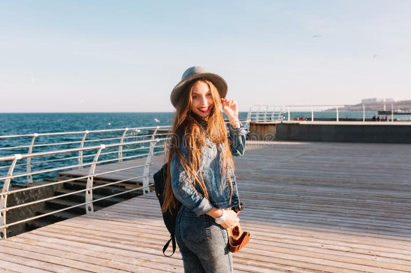 Slim stylish brunette girl in hat and denim outfit having fun at sea wharf in morning. Female photographer with black stock photography