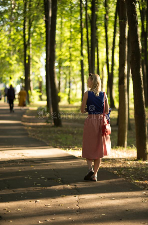 Slim tall girl with blond hair in a blue top and a light skirt, in black sandals walks in the Park. Vertical photography. rear stock photos