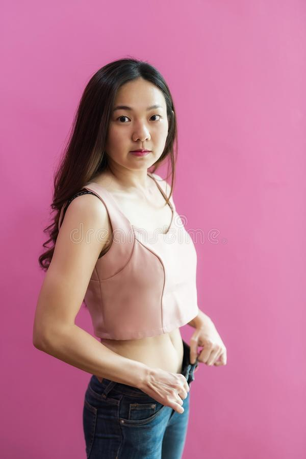 Weight loss by show slim waist with old jeans. Slim Waist of Young Asian Woman with perfect healthy thin body on pink background with copy space for text royalty free stock image