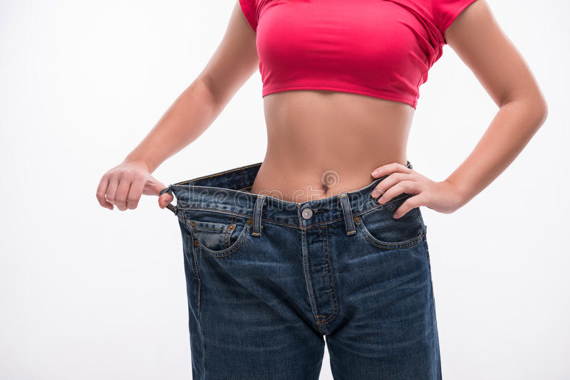 Slim waist of young woman in big jeans showing stock photos