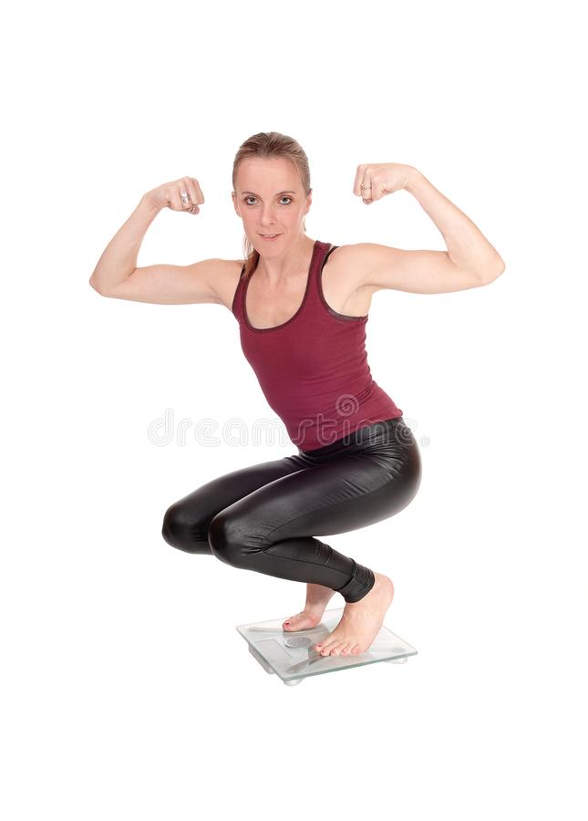 Slim woman crouching on a scale flexing muscles. A young slim woman in black leather pants crouching on a scale flexing her muscles in her arms, isolated for royalty free stock photos