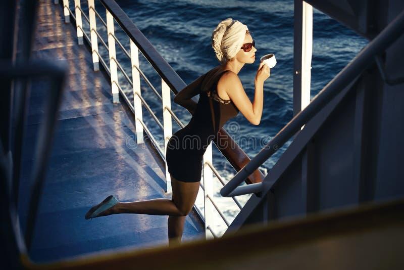 Slim woman drinking coffee on the board stock photos