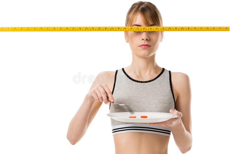 slim woman eating cherry tomato with measuring tape in front her eyes royalty free stock image