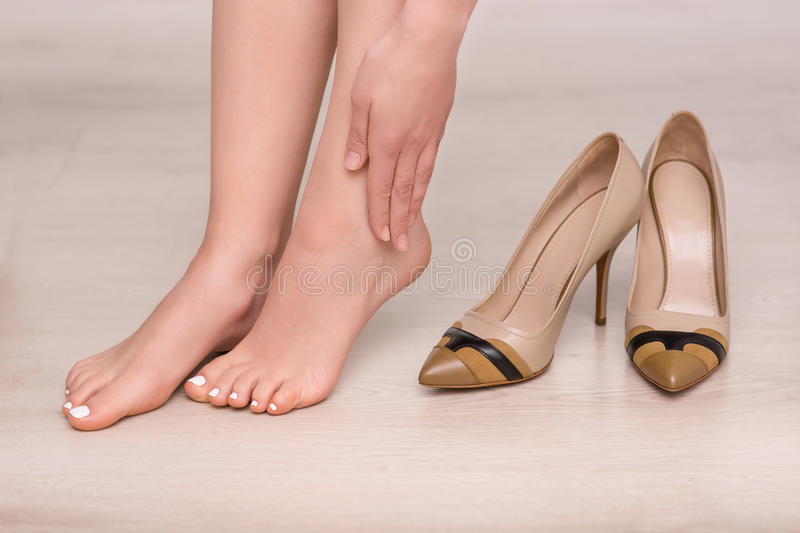 Slim woman going to wear shoes royalty free stock photography