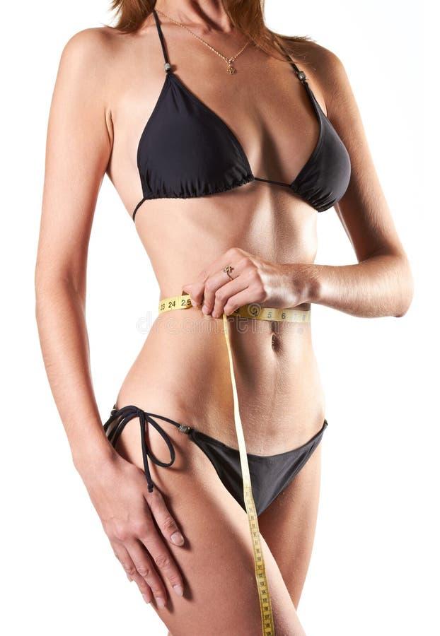 Slim woman measuring waist with tape measure stock photo