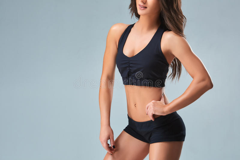 Slim woman`s body over grey background. Beautiful woman in black shorts and sports top stock photography
