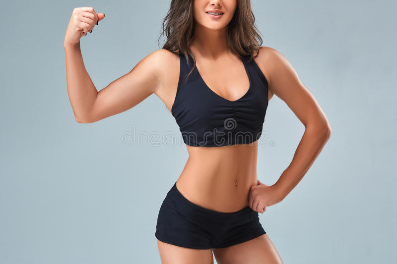 Slim woman`s body over grey background. Beautiful woman in black shorts and sports top stock image