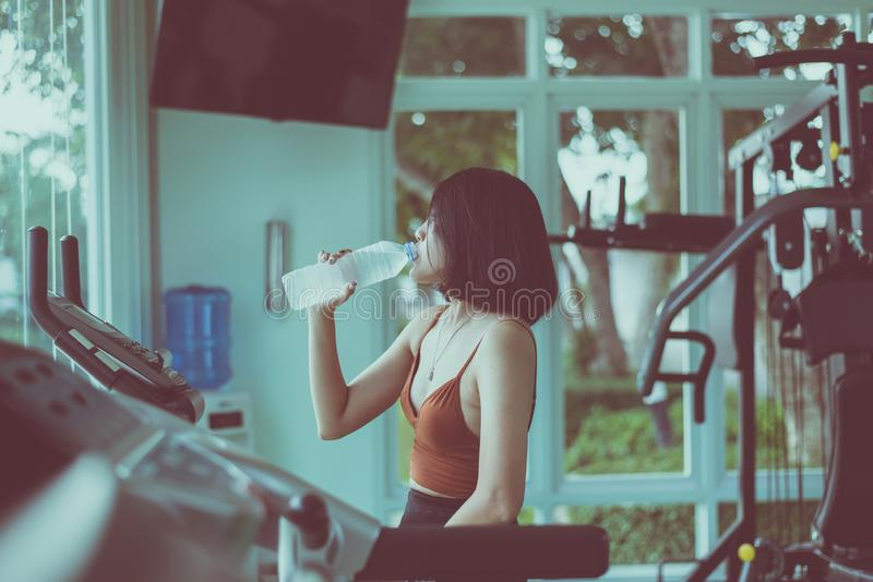 Slim woman sitting and drinking water in gym,Asian female break and relax after workout stock photo