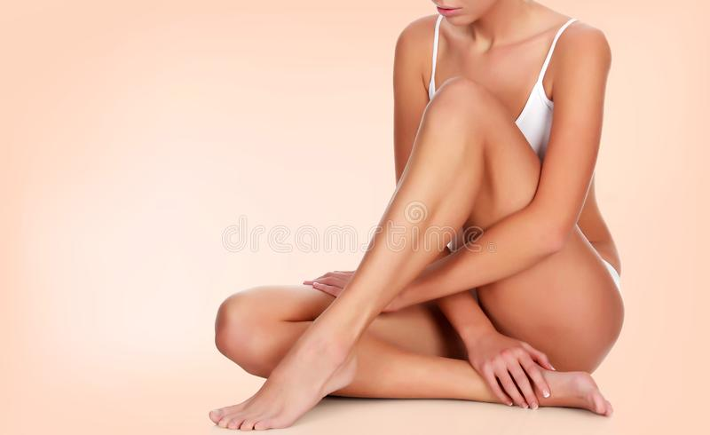 Woman touches her smooth skin on legs royalty free stock image
