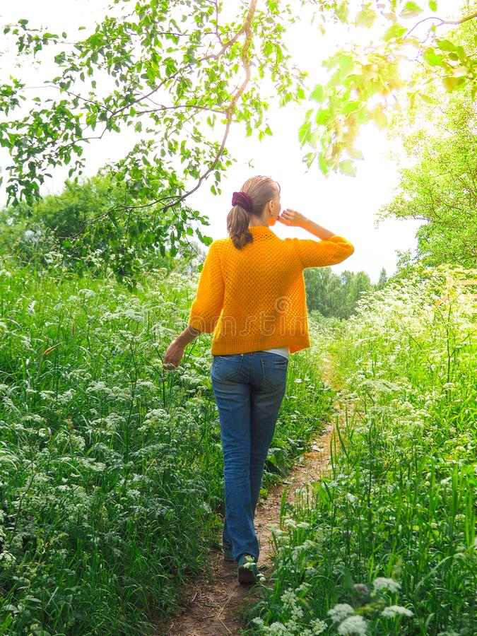 Slim woman traveler in yellow jacket for a walk among the green grass. royalty free stock image