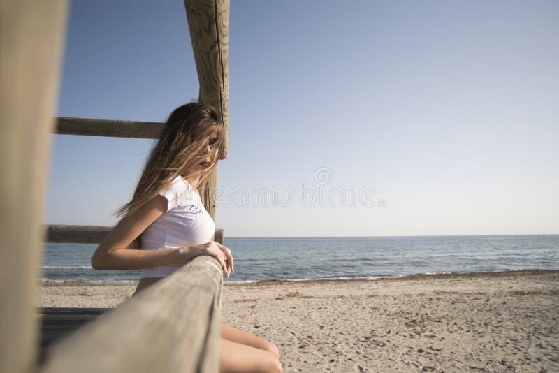 Slim woman wear bikini sitting on wooden guard tower royalty free stock image