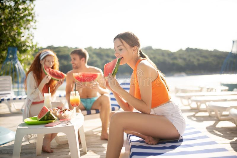 Slim woman wearing orange shirt eating watermelon stock images