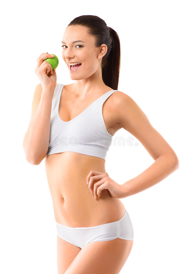Slim woman in white underwear with green apple at royalty free stock photography