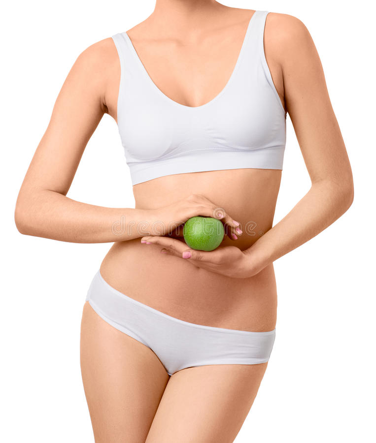 Slim woman in white underwear with green apple at stock photos