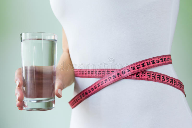 Slim woman in white underwear holds a glass of water in her hand, at the waist measuring tape. Concept of slimness stock image