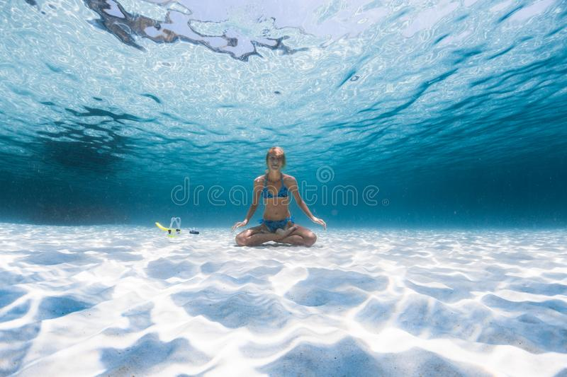 Slim yogi lady. Sits on the sandy sea bottom in the relaxed Lotus pose, smiles and looks at the camera stock image
