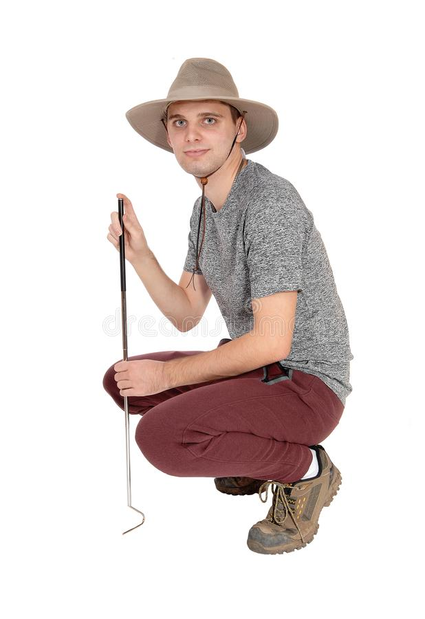 Young man crouching in safari hat. A slim young man in a gray sweater with a safari hat and a tool to catch.some snags crouching on the floor, isolated for white stock images