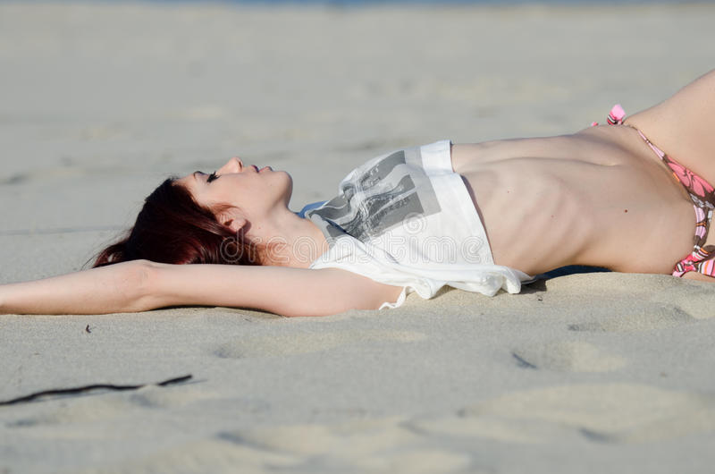 Slim young red hair woman wearing bottom bikini and shirt royalty free stock images